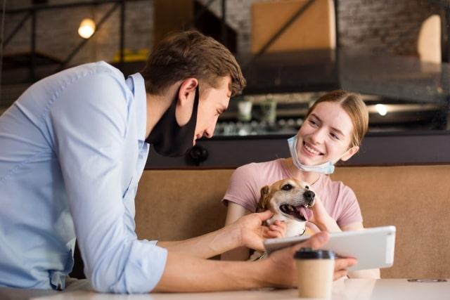 カフェで談笑する人と犬